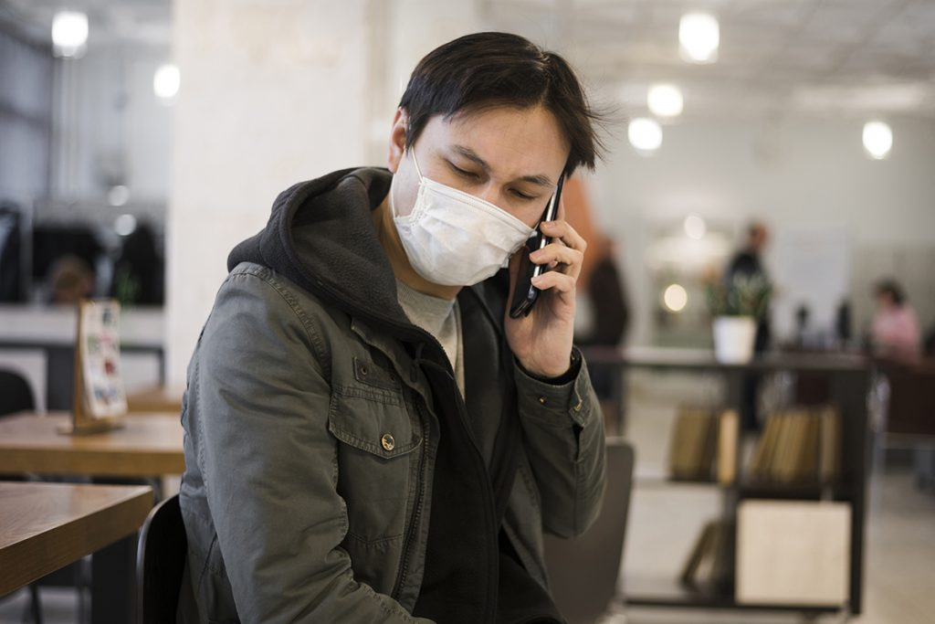 Asian man with mask on using his cellphone